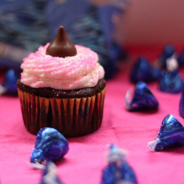 One pink Hershey's Chocolate Coconut Creme Kisses Cupcake in front of bag of Kisses