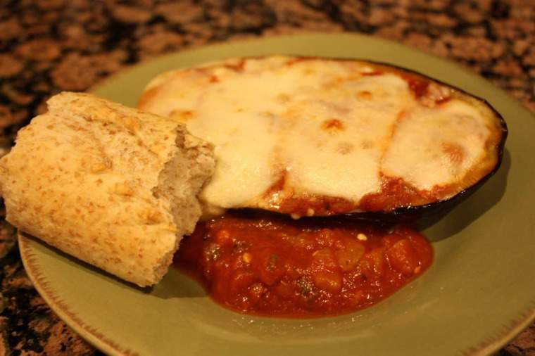 Eggplant Parmesan stuffed eggplant on plate with a roll
