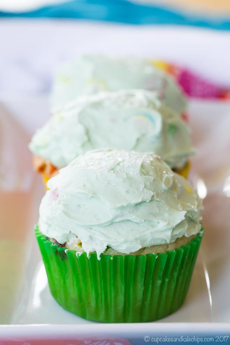 three lucky charms cupcakes on a white rectangular plate