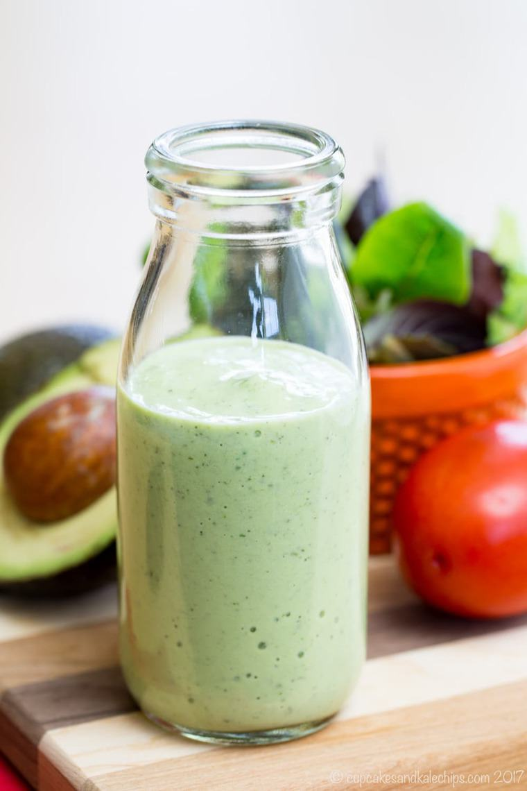 A glass bottle filled with homemade avocado ranch dressing