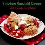 This chicken souvlaki recipe features chicken skewers, feta tomato salad, pita, and hummus.