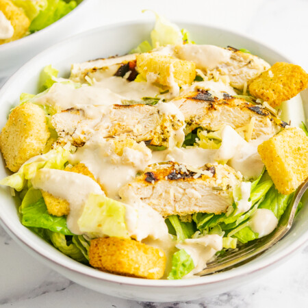 Chicken Caesar Salad in a white salad bowl with a fork