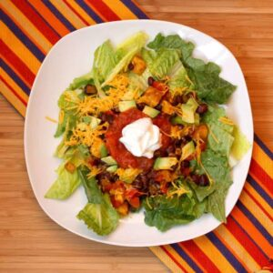 This healthy taco salad recipe has back beans, avocado, sour cream, salsa, and lettuce.