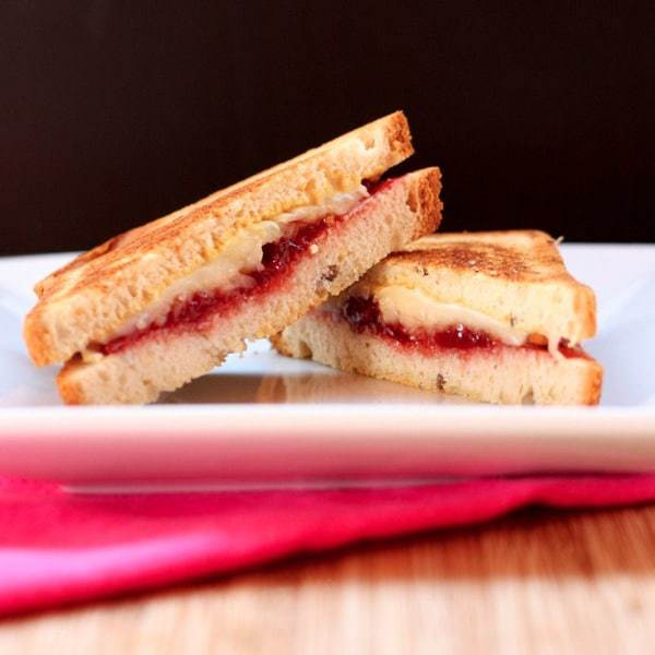 A Close-Up Shot of a Havarti Grilled Cheese Sandwich with Bacon & Strawberry Cut Diagonally Into Two Halves
