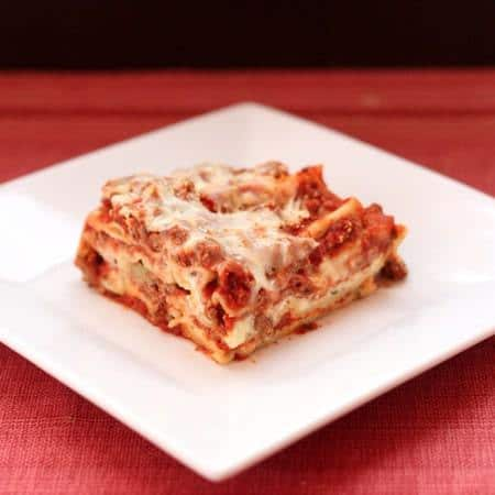 A slice of homemade lasagna on a white plate with a red background.