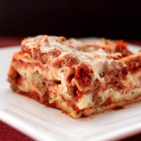 A slice of lasagna on a white plate.