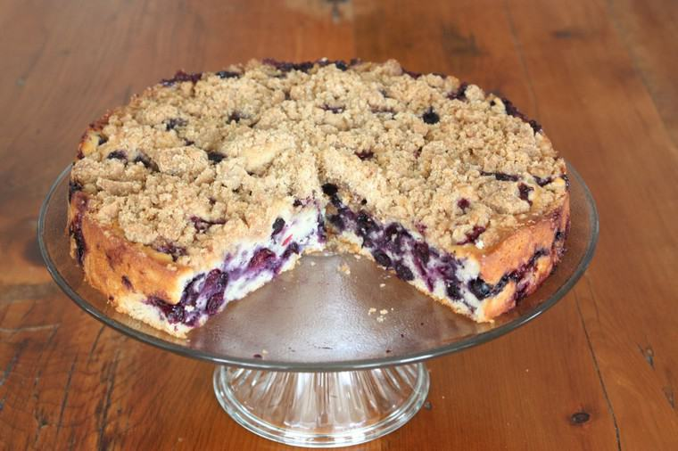 Three quarters of a blueberry buckle coffee cake with crumb topping on a cake pedastal