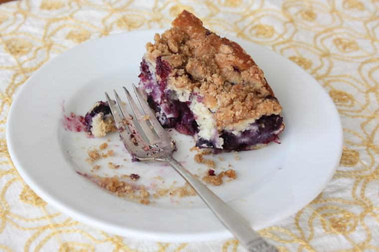 A partially eaten slice of Blueberry Buckle coffee cake on a plate with a fork