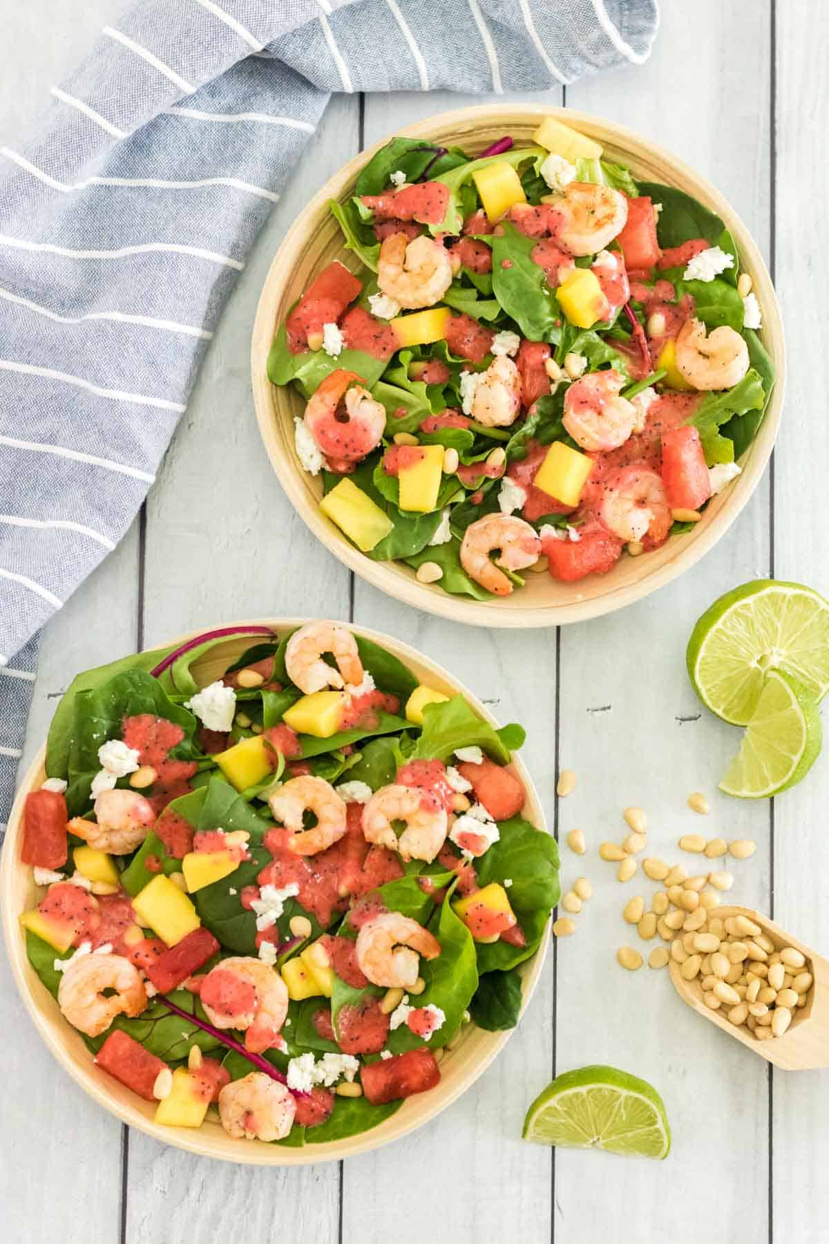 looking down on two bowls of salad with grilled shrimp and summer fruit next to a scoop of pine nuts and lemon wedges