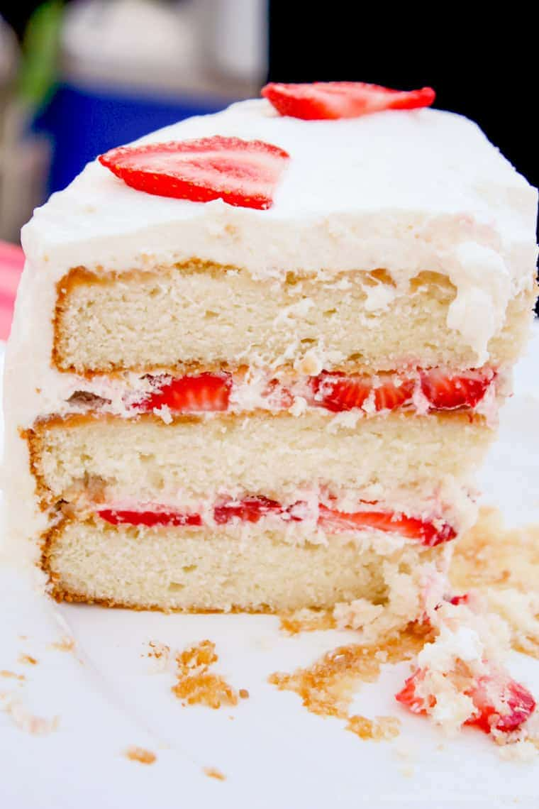 A slice of white layer cake with fresh strawberry cake filling and homemade whipped cream