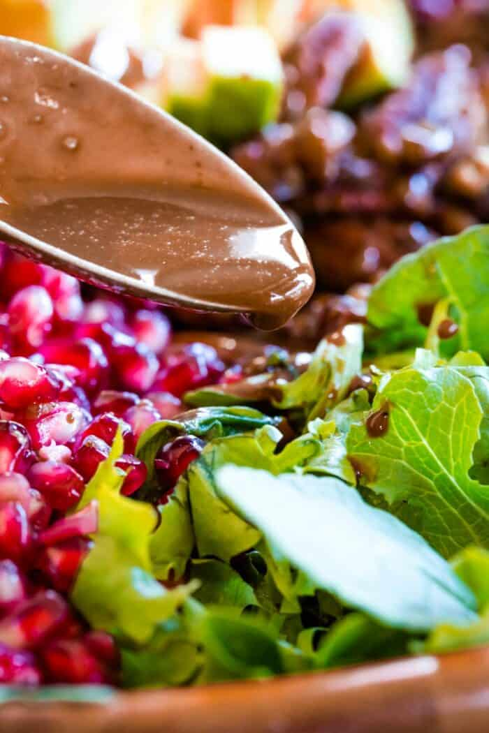 Drizzling the cranberry vinaigrette off a spoon onto a salad