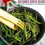 Balsamic Shallot Green Beans in a Skillet being picked up with wooden tongs