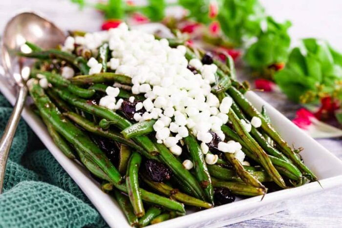 Balsamic Green Beans with Cranberries on a white rectangular serving dish topped with goat cheese