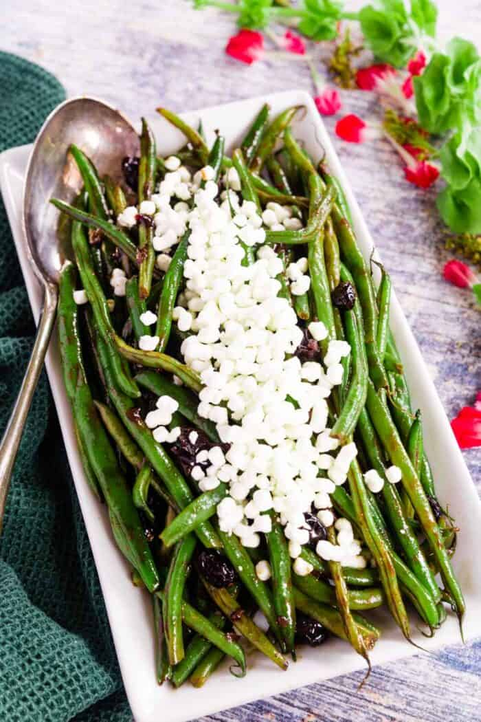 A white rectangular platter full of balsamic glazed green beans with a silver serving spoon