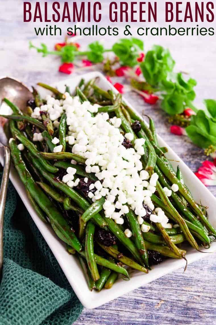 A serving platter with Balsamic Green Beans with Cranberries and crumbled goat cheese on top