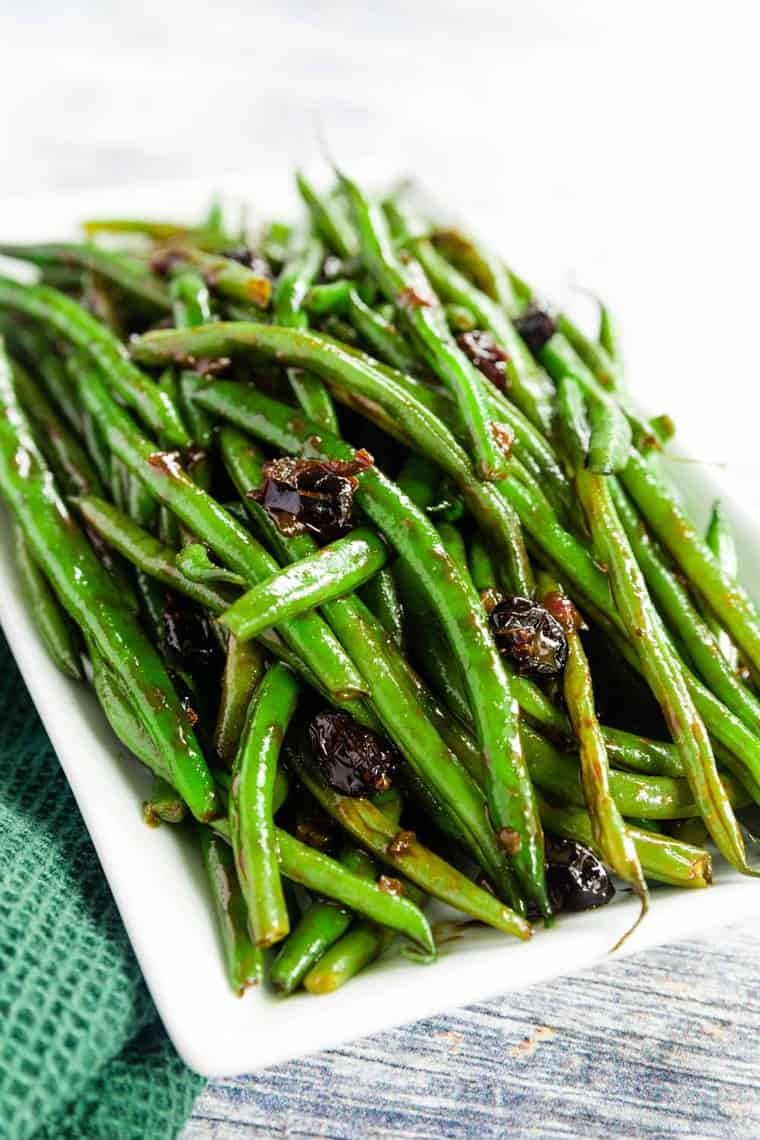 Balsamic Glazed Green Beans with Dried Cranberries piled on a white plate