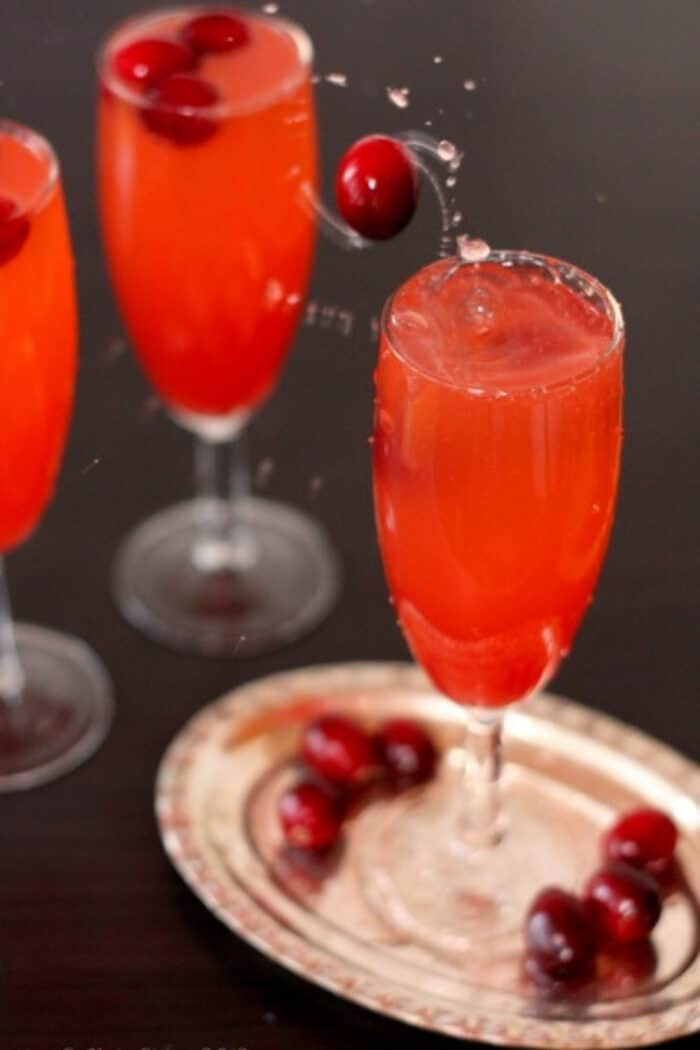 Dropping fresh cranberries into a Cranberry Fizz Mocktail