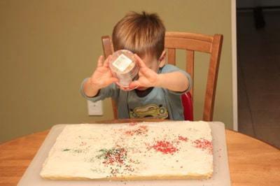 Kid sprinkling colored sugar on a pan of cookie bars