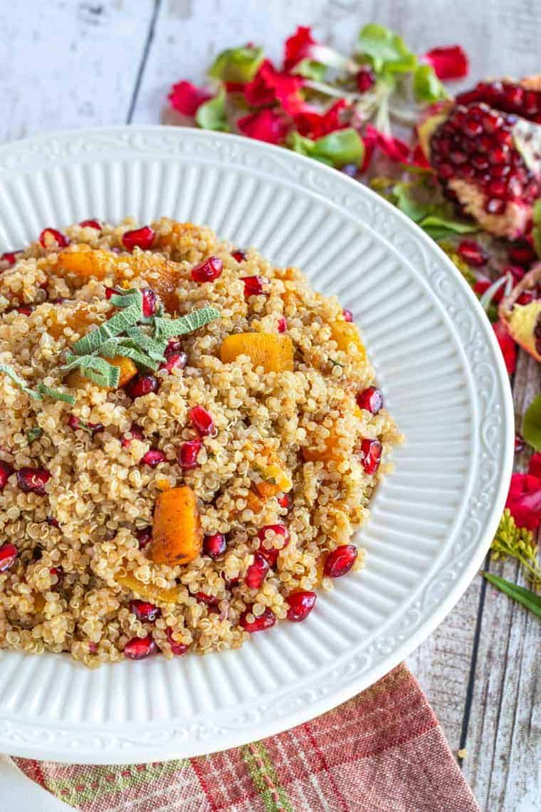 A bowl of quinoa with roasted butternut squash cubes and pomegranate seeds