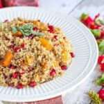 Bowl of butternut squash and pomegranate quinoa topped with sage