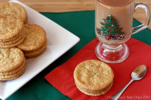 Snickerdoodles on a white plate with three on a red napkin with a cup of tea