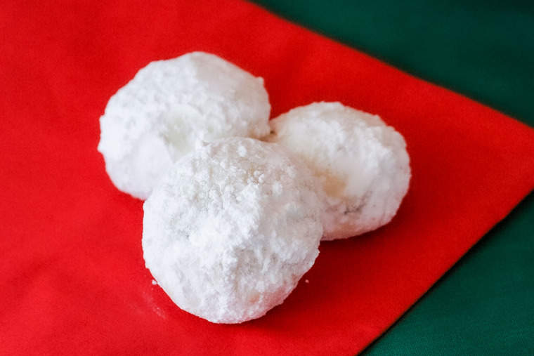 Three snowball cookies on a red napkin and green tablecloth