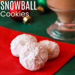 Three snowball cookies on red and green napkins with a cup of tea