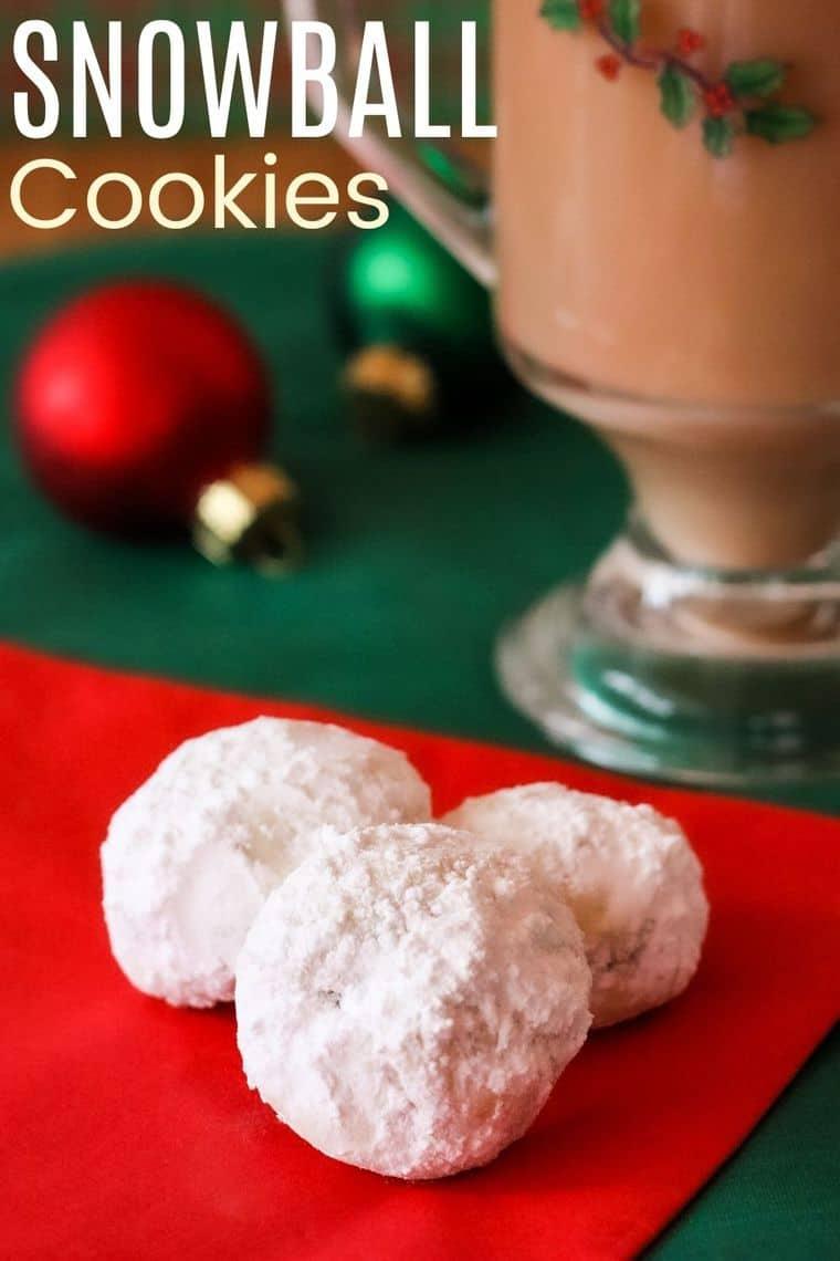 Three snowball cookies with a holiday mug of tea