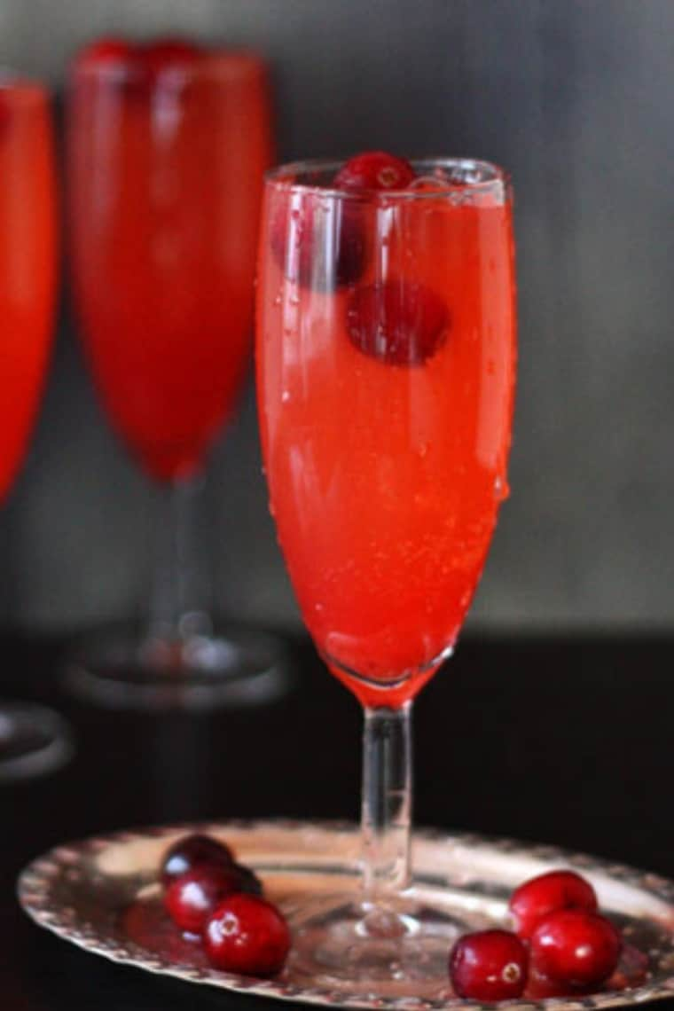 Red Mocktail in a champagne glass surrounded by fresh cranberries