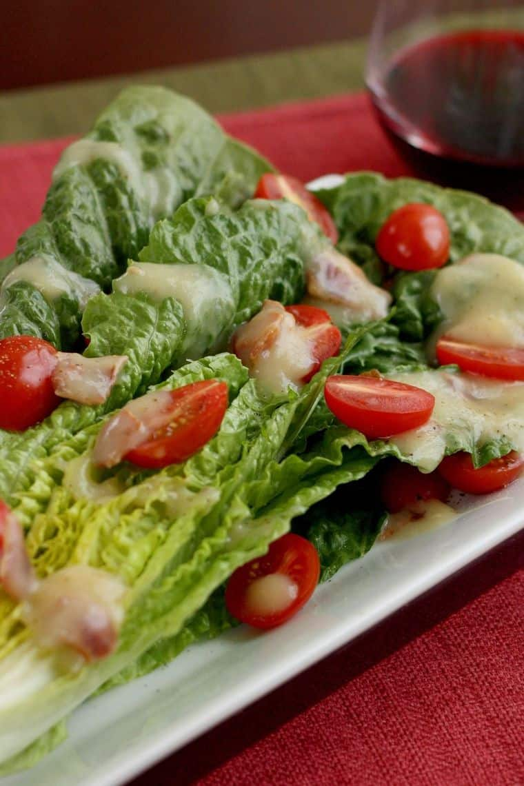 Half a head of romaine lettuce drizzled with hot maple bacon dressing and topped with halved grape tomatoes