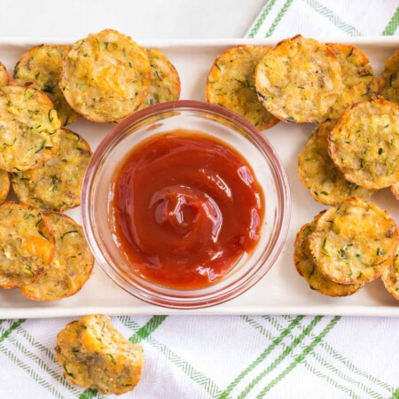 Zucchini Potato Tots on a rectangular platter with a bowl of ketchup