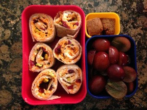Whole wheat tortillapinwheeles with cream cheese, shredded carrots, pistachios, and dried cranberries, grapes, homemade graham crackers