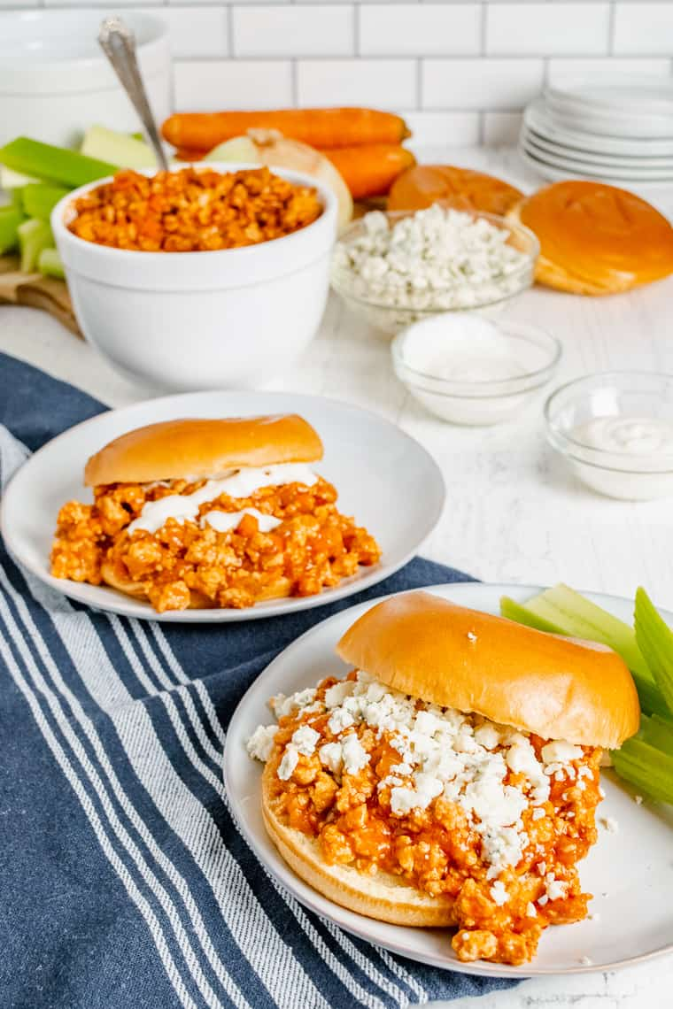 Two Buffalo Chicken Sloppy Joe Sandwiches one with blue cheese on top and the other with ranch dressing