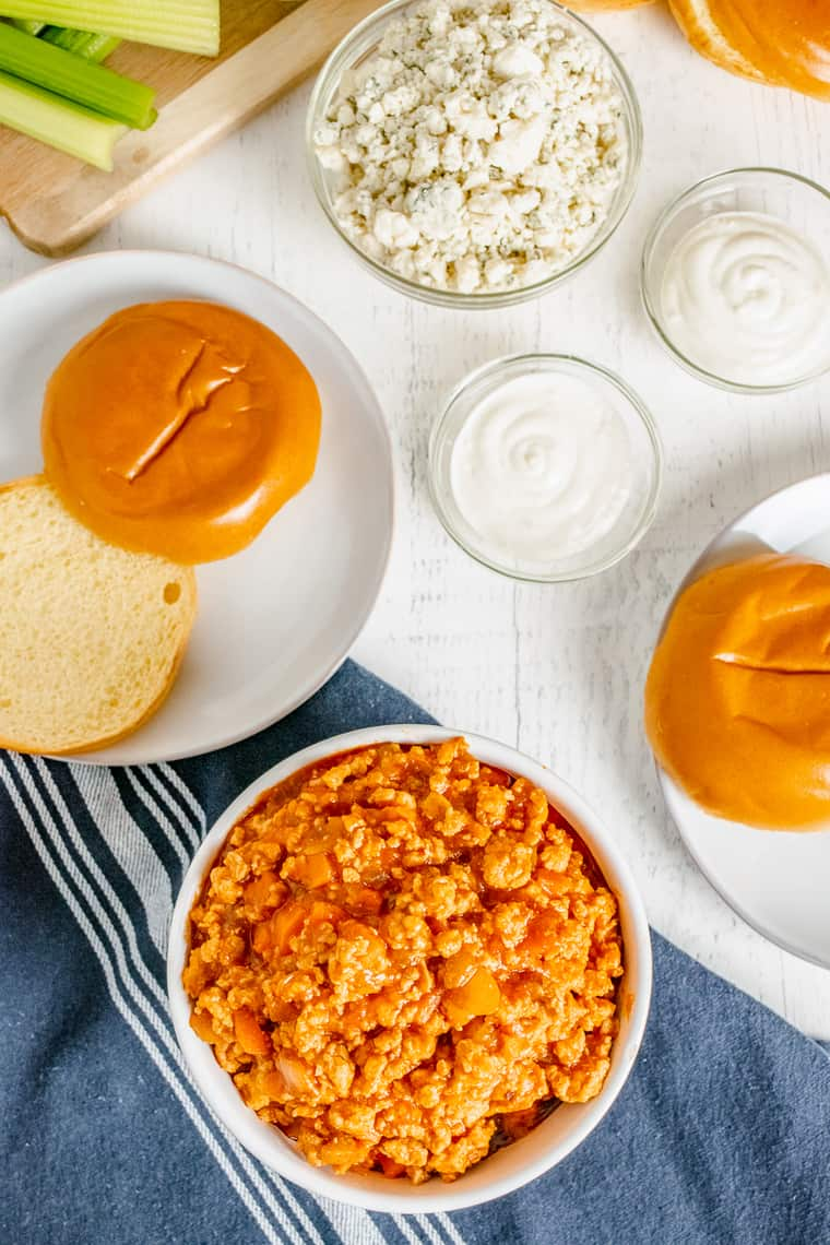 Buffalo chicken sloppy joes ground chicken mixture in a bowl with rolls nearby on plates and blue cheese and ranch dressing in bowls