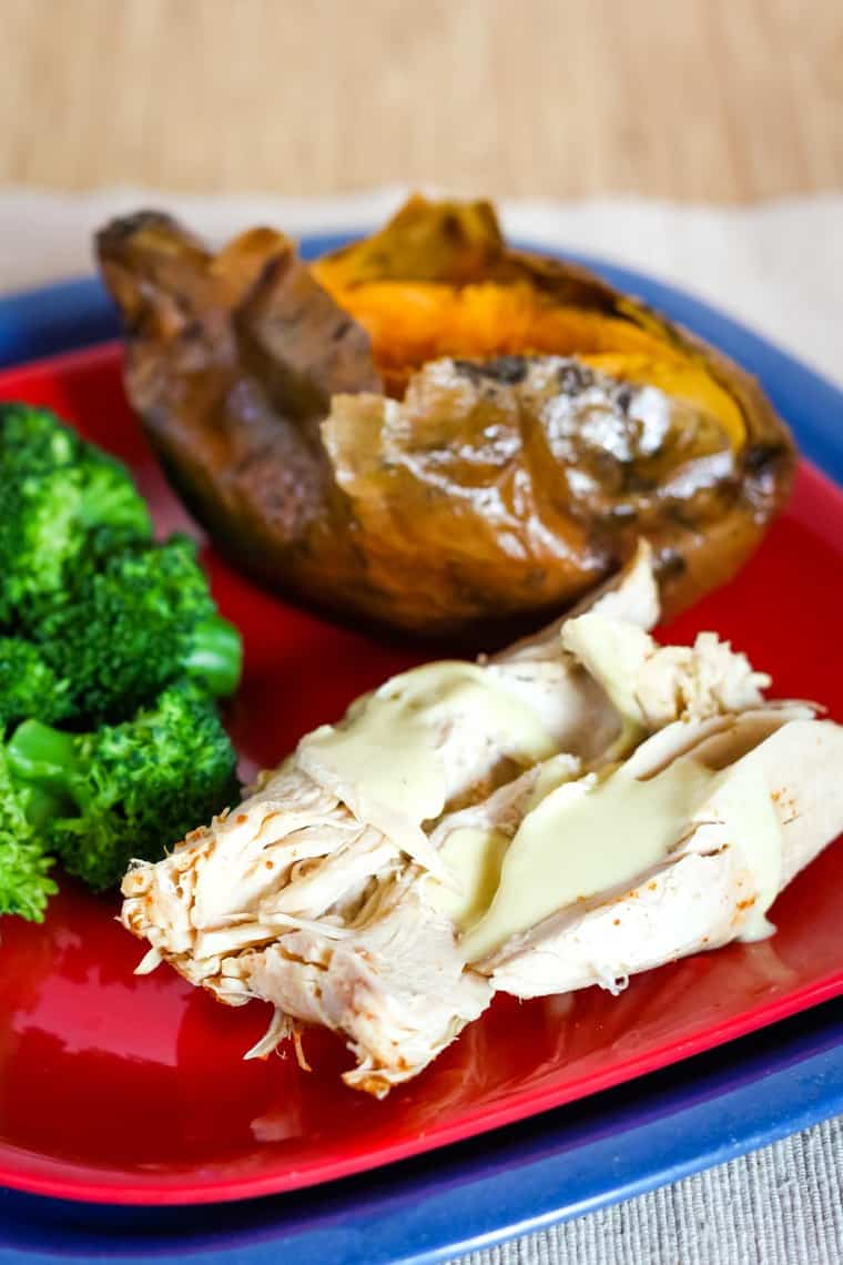 Red plate with slow cooker turkey breast slices served with sweet potato and broccoli