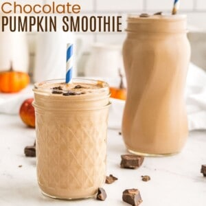 two chocolate pumpkin smoothies in glass jars with striped straws surrounded on the countertop by bits of chocolate