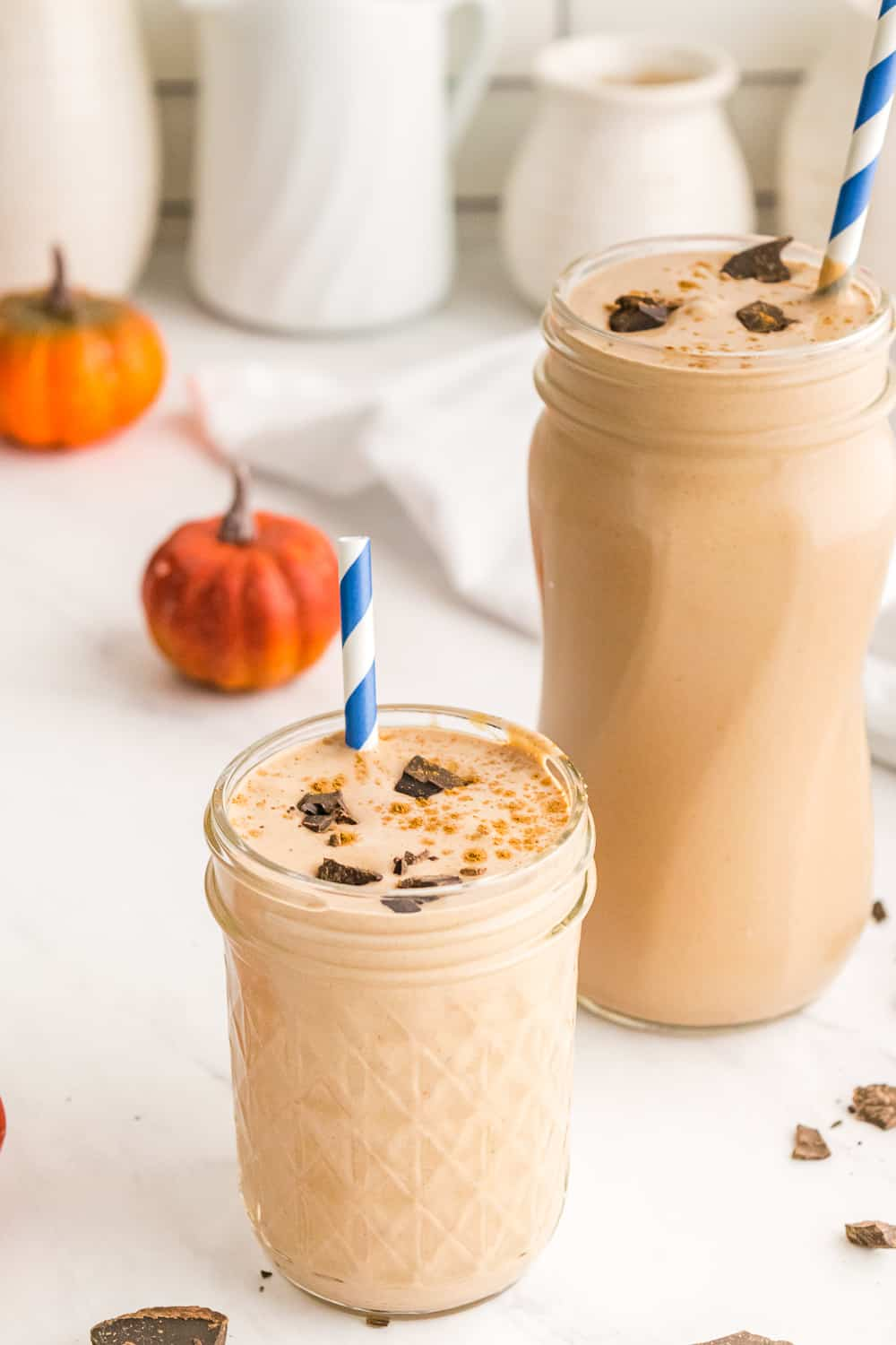 two chocolate pumpkin spice smoothies in glass jars surrounded by bits of chocolate and mini pumpkin decorations