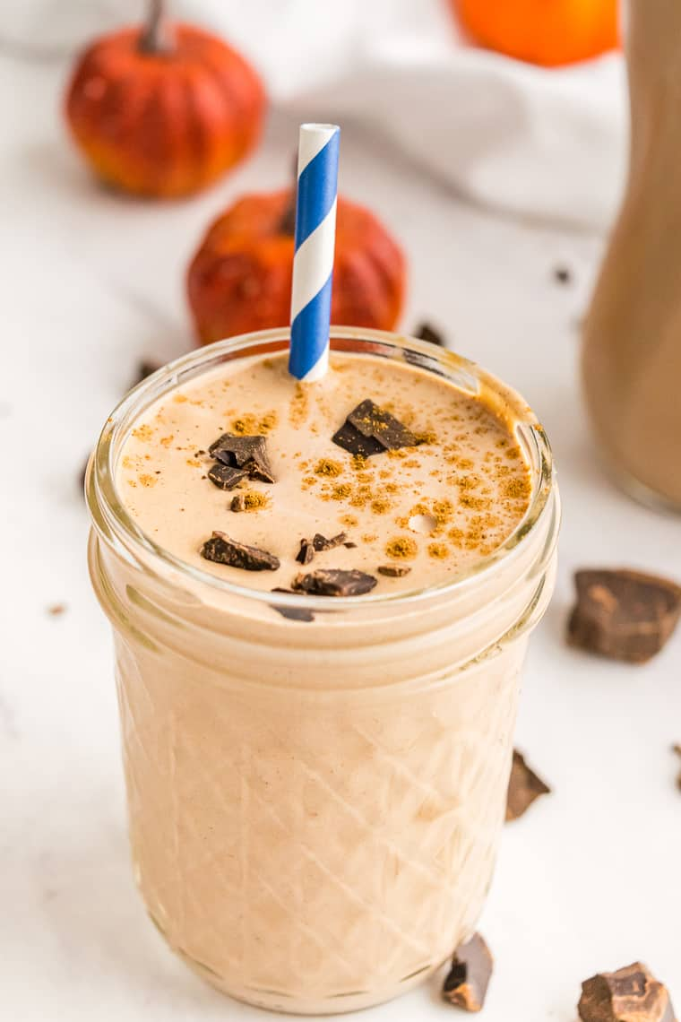 A Chocolate Pumpkin Smoothie in a jelly jar with a sprinkle of pumpkin pie spice and bits of chocolate on top and a blue and white striped straw