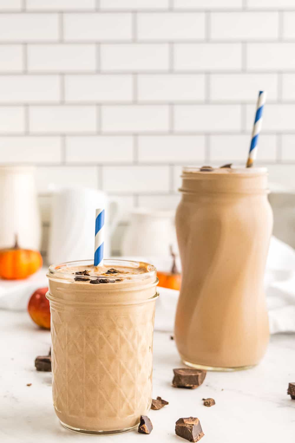 Two pumpkin chocolate smoothies on a counter in front of a white tile wall with pieces of chocolate around them