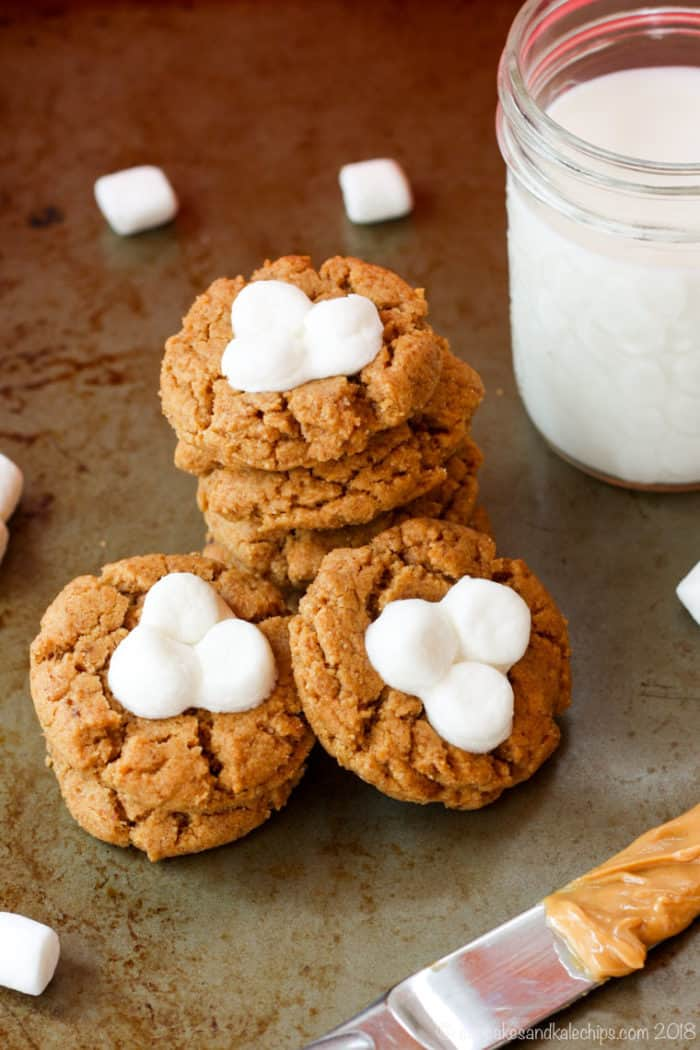 a pile of peanut butter cookies, each topped with three mini marshmallows