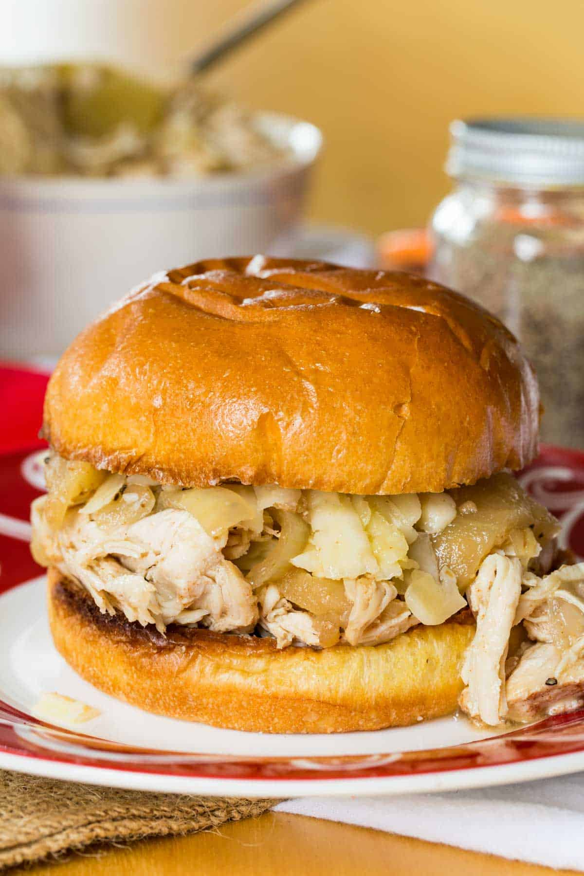 Slow Cooker Apple Cider Chicken shredded and piled on a brioche bun with cheddar cheese