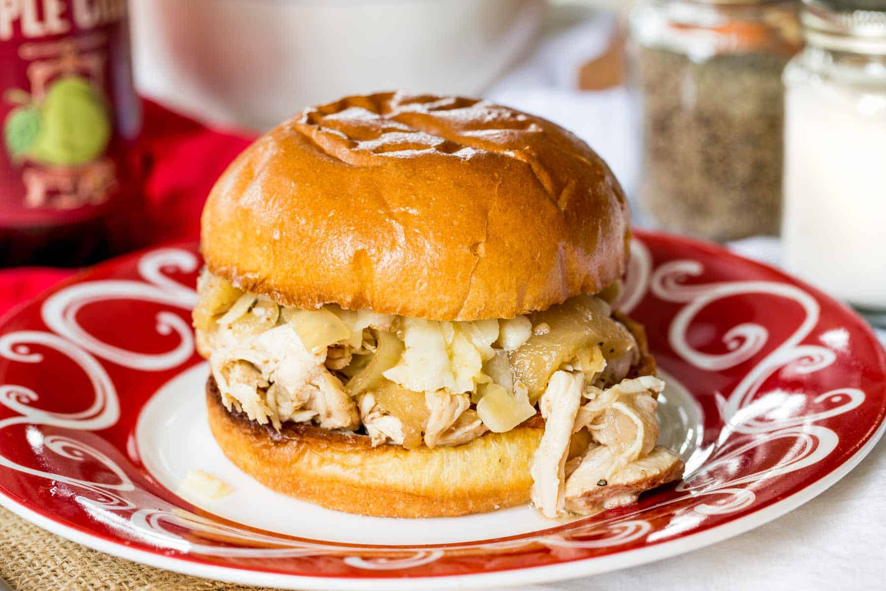 Slow Cooker Apple Cider Pulled Chicken Sandwich on a red and white plate
