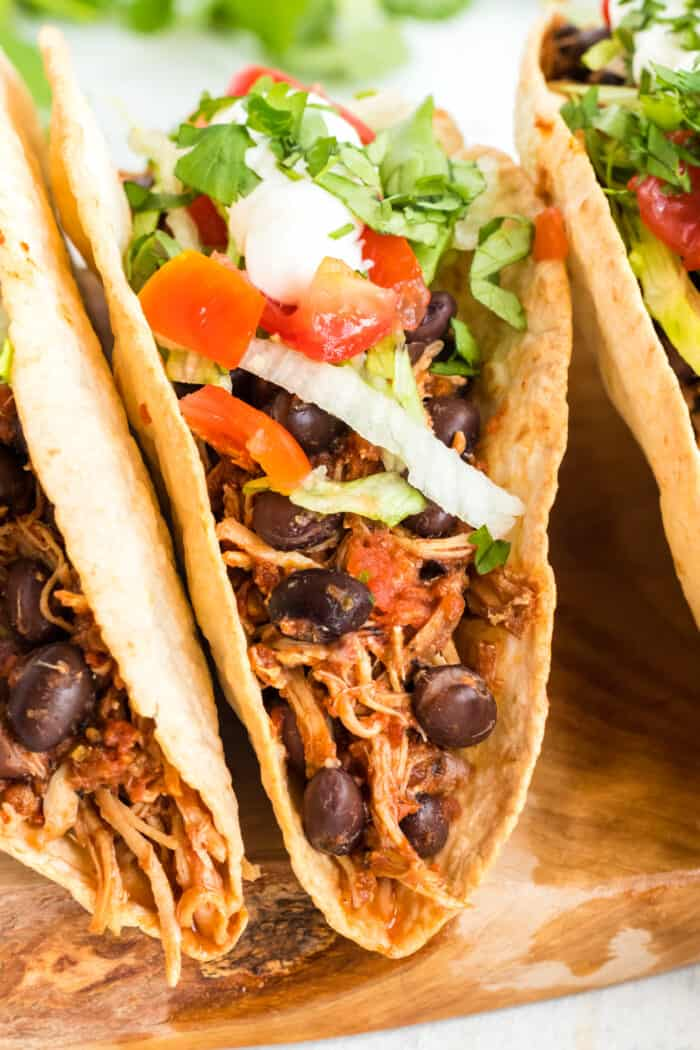 Tacos filled with shredded chicken, black beans, lettuce, tomatoes, and sour cream