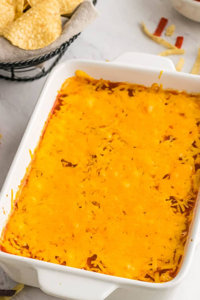 hot dip with melted cheese on top in a white baking dish