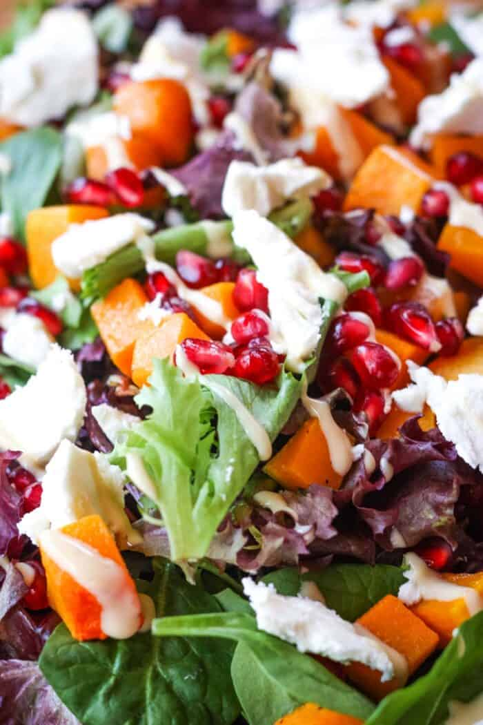 Mixed spring greens with cubed of butternut squash, pomegranate arils, and crumbled goat cheese