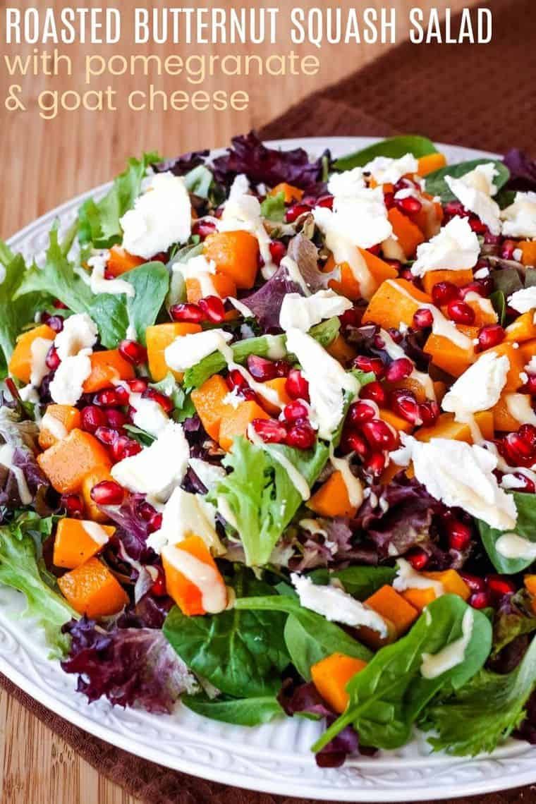 Salad topped with butternut squash, pomegranate seeds, crumbled blue cheese, and a creamy dressing