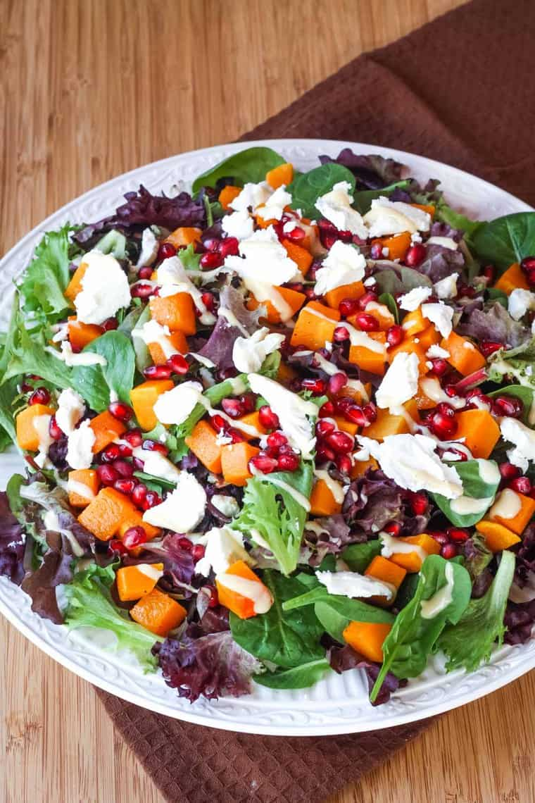 Large dinner plate filled with baby greens, roasted butternut squash cubes, pomegranate, and salad dressing