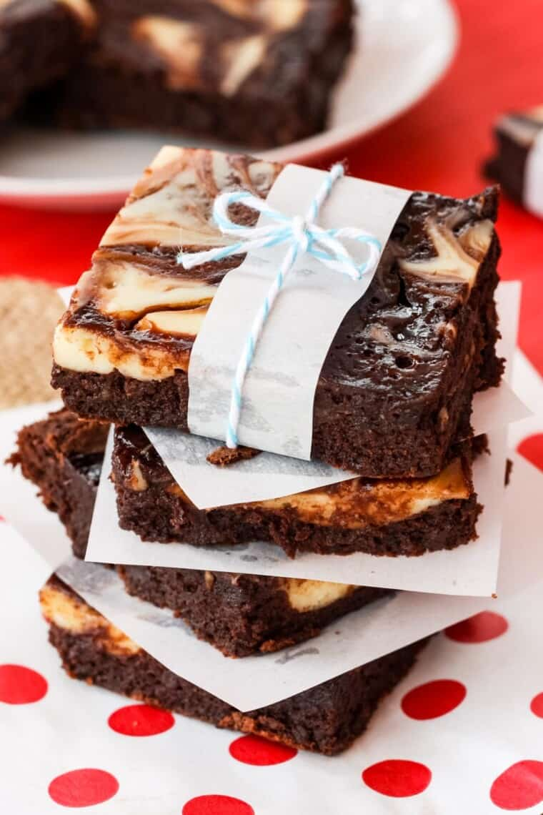 stack of three nutella cheesecake brownies, each wrapped with a strip of wax paper and twine