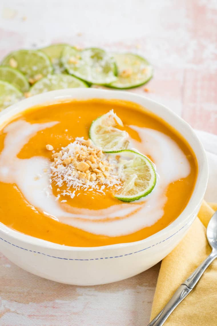 Curried Butternut Squash Soup swirled with coconut milk and garnished with grated coconut and chopped peanuts