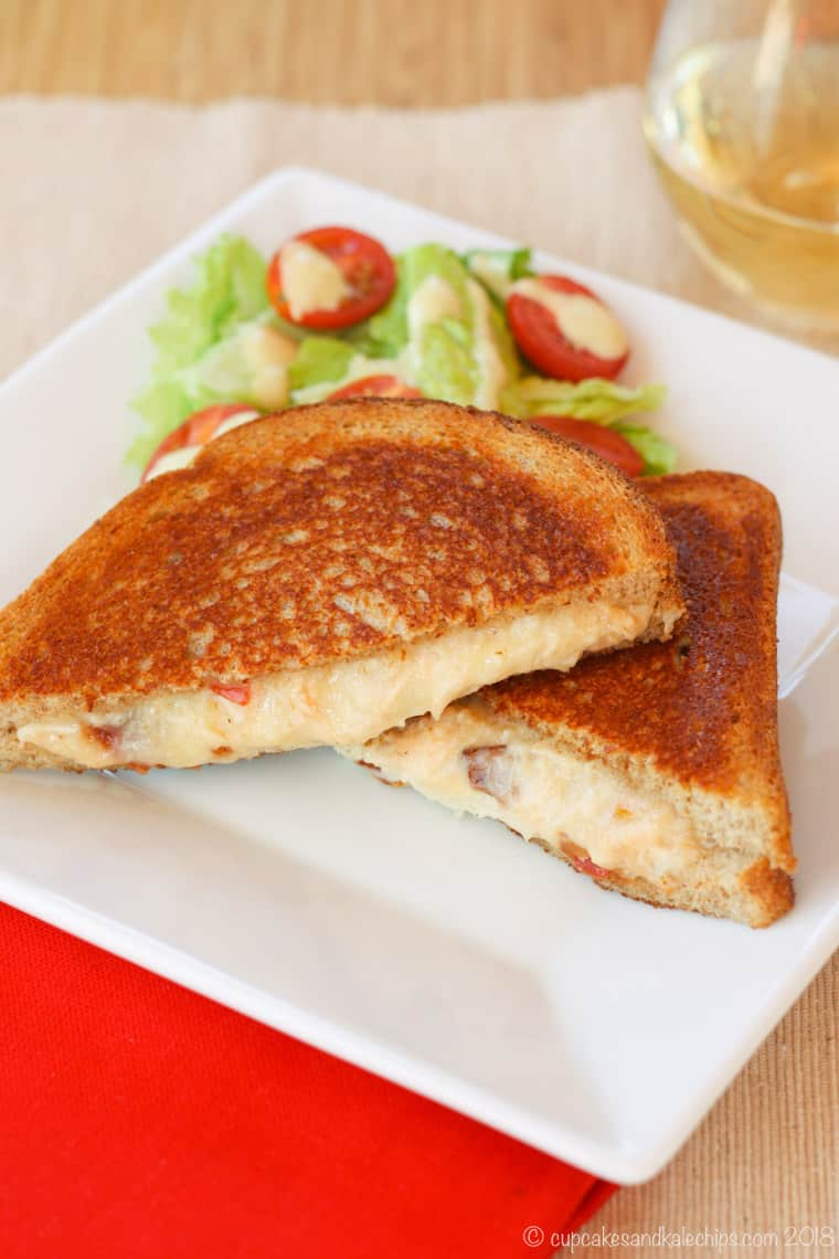 Grilled cheese with oozing cheesy filling flecked with bacon on a white plate